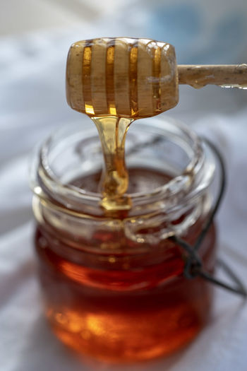 Close-up of honey in glass jar on table and wooden honey dipper