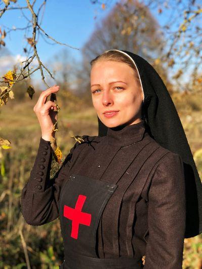 Portrait of nun standing on field