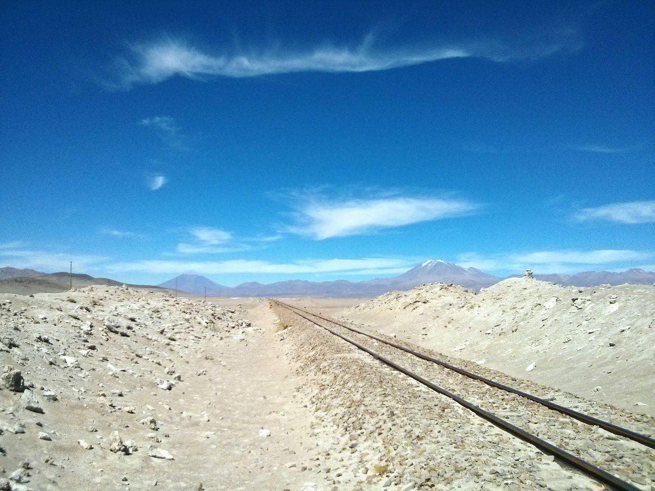 Railroad Track In Desert Against Blue Sky