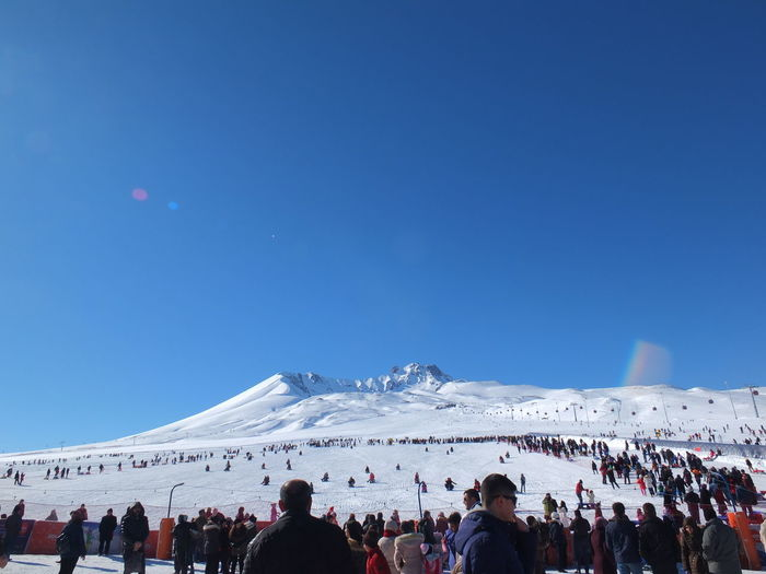 People at town square during winter against clear blue sky