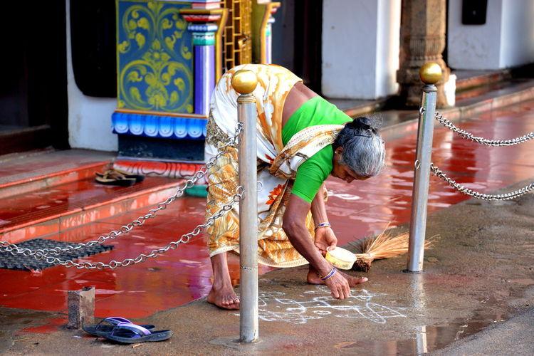 Woman making rangoli outside house
