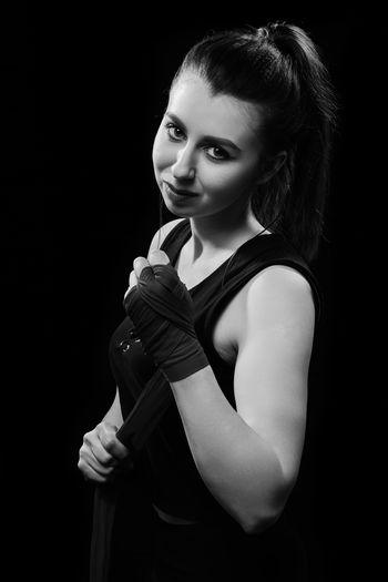 Portrait of female boxer wearing bandage against black background