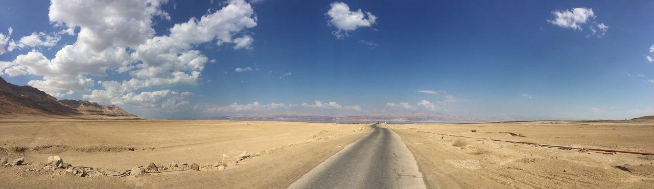 Panoramic view of desert road against sky