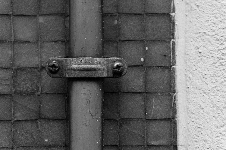 Close-up of pipe clamp mounted on wall