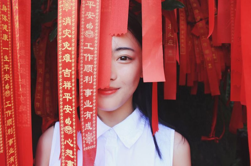 Close-up portrait of young woman amidst red ribbon
