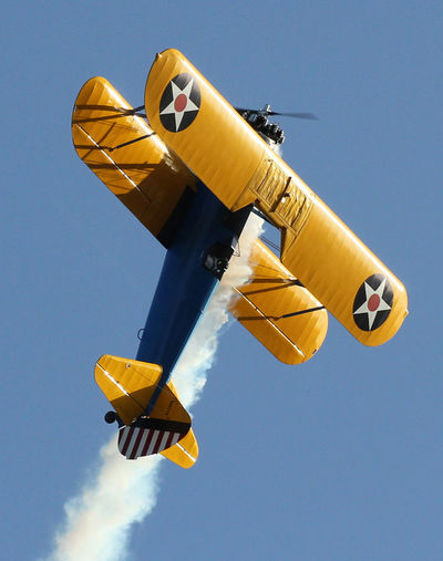 Low angle view of biplane flying in clear sky