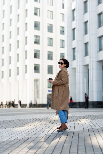 Pretty woman goes to work in the business center in stylish clothes with a glass of coffee.