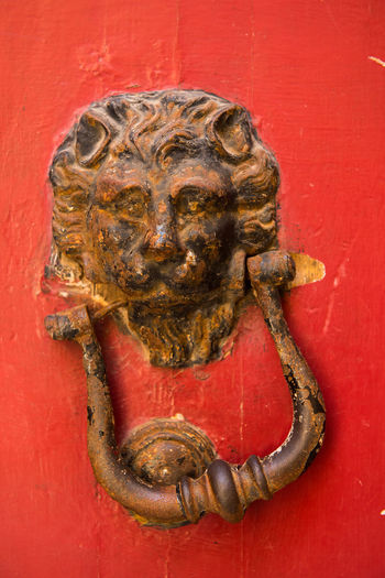 Old rusty iron lion head door knocker on a red door. Valletta, Malta Bronze Entrance Iron Lion Lion Head Malta Ornament Valletta,Malta Brass Close-up Detail Door Doorway HEAD Knob Knocker Knocking Lock Mettalic No People Object Old Rusty Vintage Wooden Door