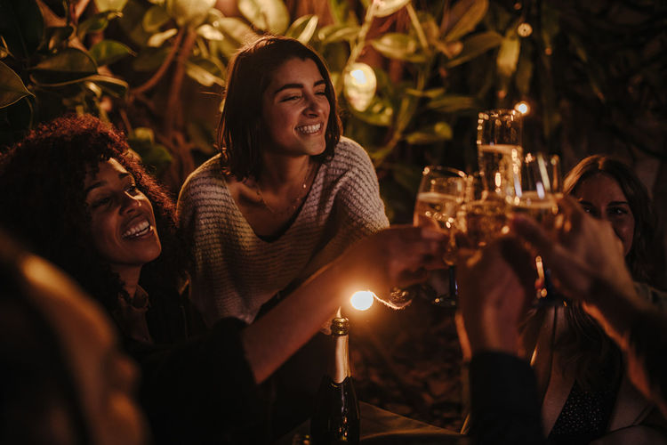 Young women toasting champagne in glass at night