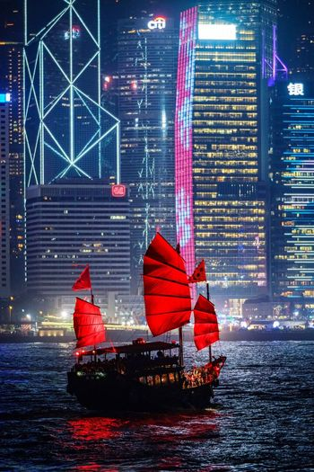 Red boat in river against illuminated buildings at night