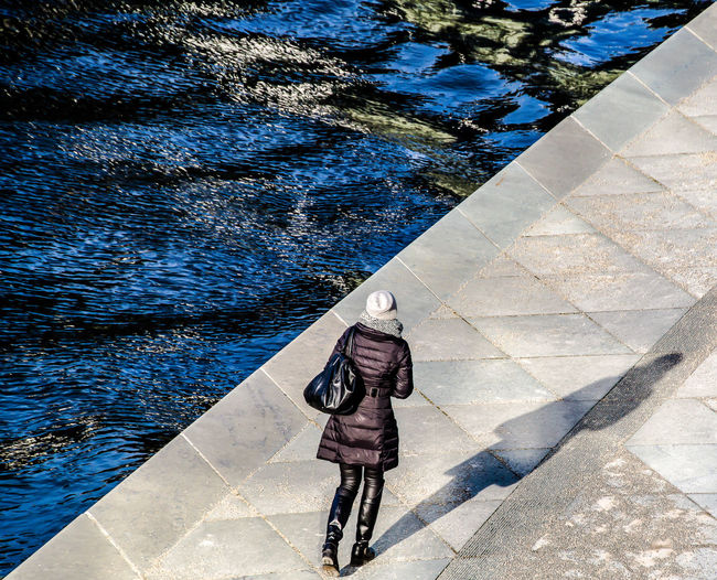 High Angle View Of Woman Walking On Promenade During Sunny Day
