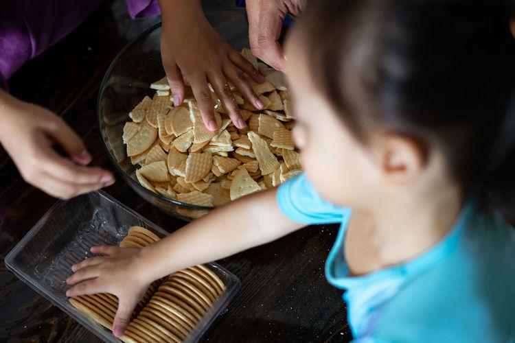 Kids making kek batik or malaysian triple chocolate dessert. crushing the cookies into tiny pieces