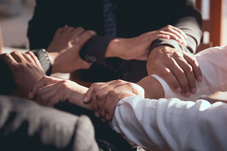 Midsection of colleagues holding hands in office