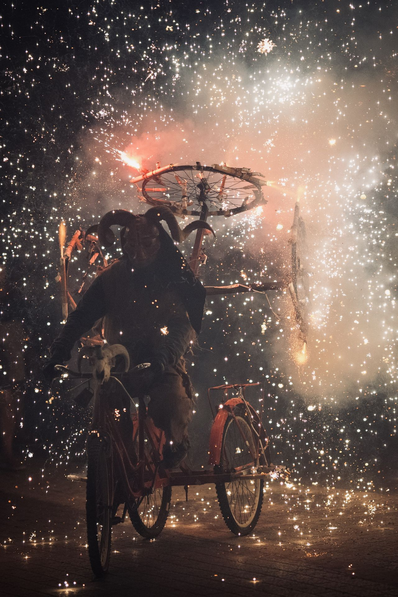 Bicycles parked in city at night fireworks at dimonis festival in majorca spain