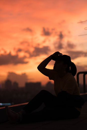 Rear view of woman photographing orange sunset sky