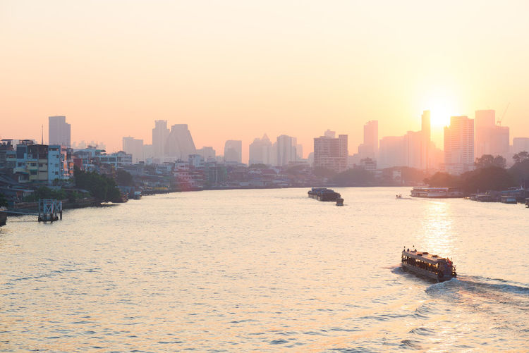 Sunrise over the scenic skyline at Bangkok, Thailand, viewed in backlight at sunrise with orange red clear sky. Boats cruising on the Chao Phraya River. Keywords: bangkok,river,cityscape,skyline,panorama,city,thailand,asia,phraya,chao,architecture,tower,travel destination,skyscraper,building,pollution,backlight,sun,sunset,residential,boat,twilight,landmark,sunshine,thai,sky,light,modern,landscape,haze,water,travel,transport,downtown,capital,background,urban,construction,business,town,dusk,office,reflection,illumination,view,transportation,corporate,tourism,famous Architecture Beach Building Exterior Built Structure City Cityscape Clear Sky Day Modern Nature No People Outdoors Sand Sea Sky Skyscraper Sunset Urban Skyline Water