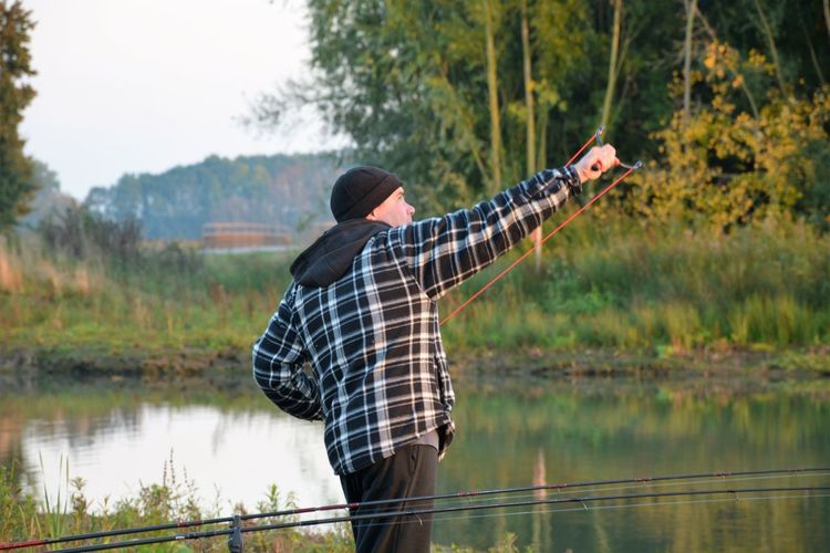 Man Using Slingshot While Standing By Fishing Rod At Lakeshore Against Trees