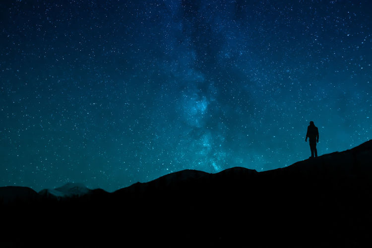 Silhouette woman standing on mountain against sky at night