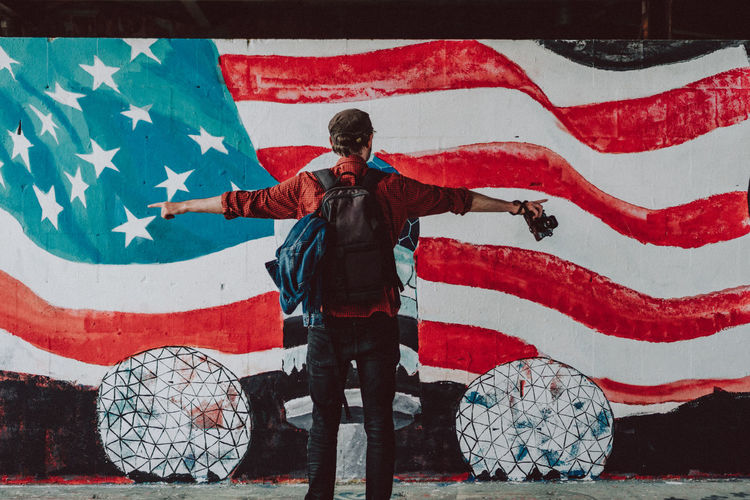 Rear View Of Man Standing Against Painted American Flag On Wall