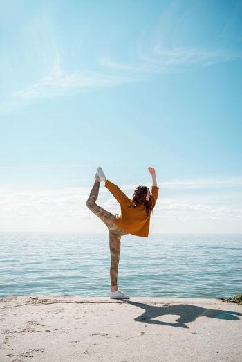 Full length of woman exercising on beach against sky