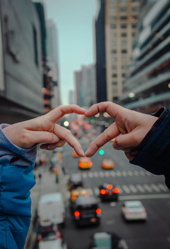 Close-up of hands making heart shape in city