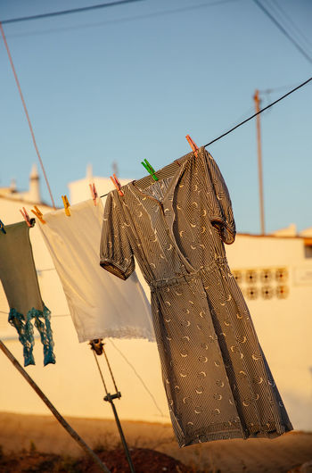 Low angle view of clothes drying on rope against sky