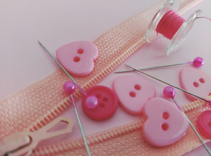 High Angle View Of Pink Sewing Items On Table