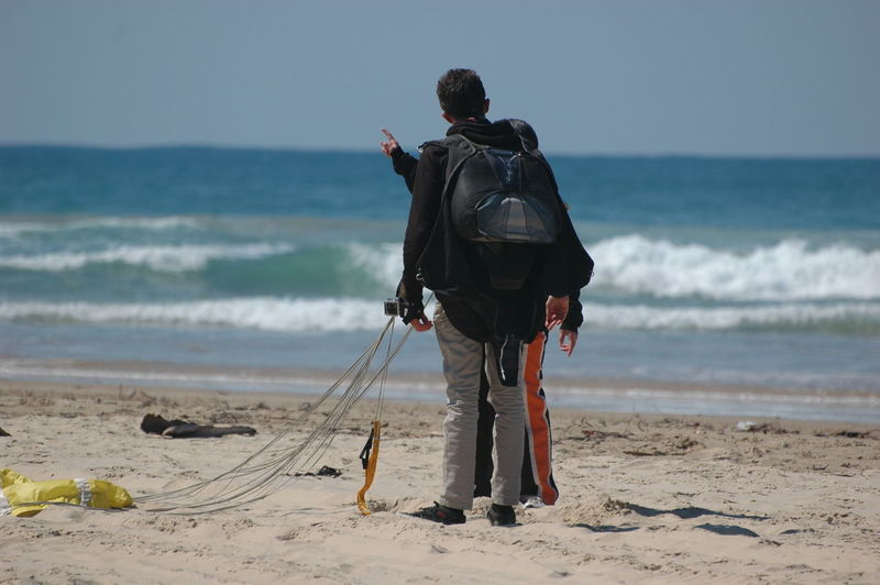 Rear view of man standing with parachute at beach