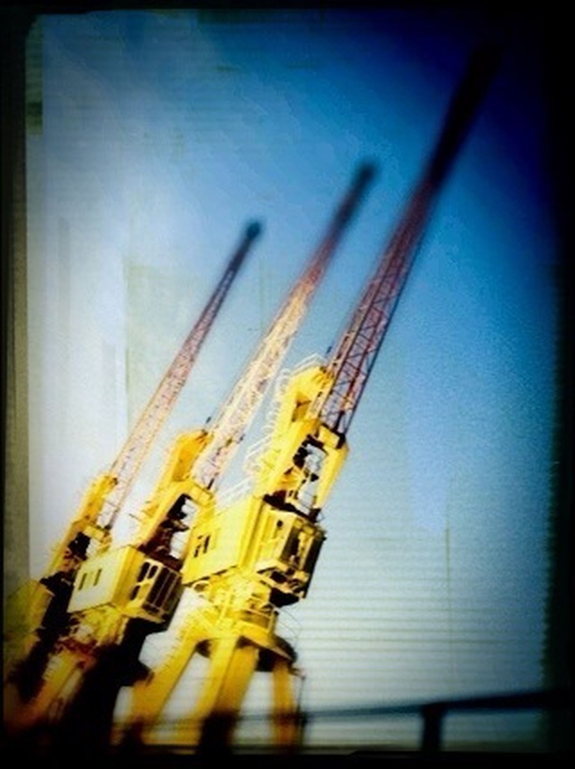 transfer print, auto post production filter, architecture, building exterior, built structure, selective focus, low angle view, no people, outdoors, sky, day, vignette, tilt, building, crane - construction machinery, city, focus on foreground, close-up, metal