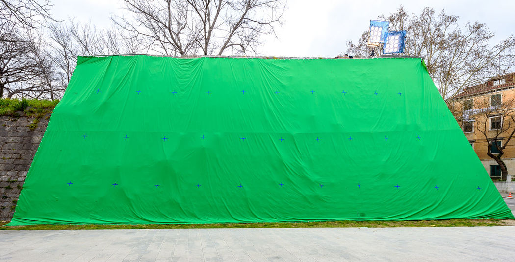 Giant green screen chroma key background on commercial set. Big green background for added special effects in post production. Effects Giant Green Green Screen Industry Movie Set Set Special Effects Architecture Bare Tree Building Exterior Chroma Chroma Key Chromakey Day Fabric Green Color Hanging Nature Pannel Postproduction