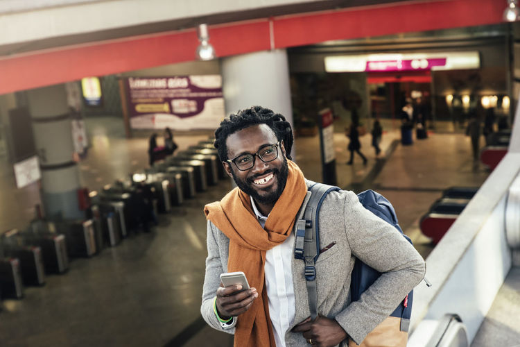 Smiling Man Using Mobile Phone While Standing At Airport