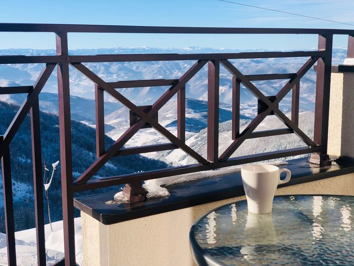 Morning coffee served on the balcony with view of the mountains Mountain Mountain Range Landscape Routine Morning Blue Sky Outdoors Terrace Balcony Table Refreshment Beverage Mug Coffee Cup Drink Snow Winter Nature Day Sunlight No People Wood - Material Architecture Sky Built Structure Vacations Trip Tourist Resort Tranquility