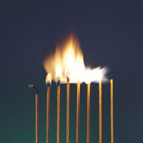 Close-up of burning matchsticks against blue background