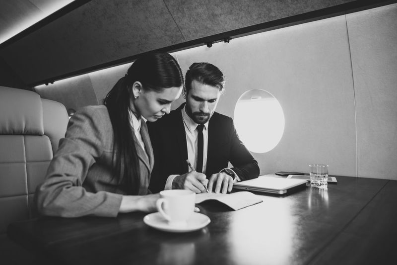 Colleagues discussing document while sitting at table in airplane