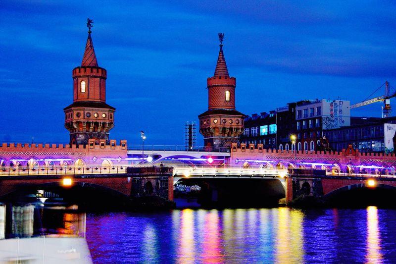 Illuminated Oberbaum Bridge Over Spree River Against Sky