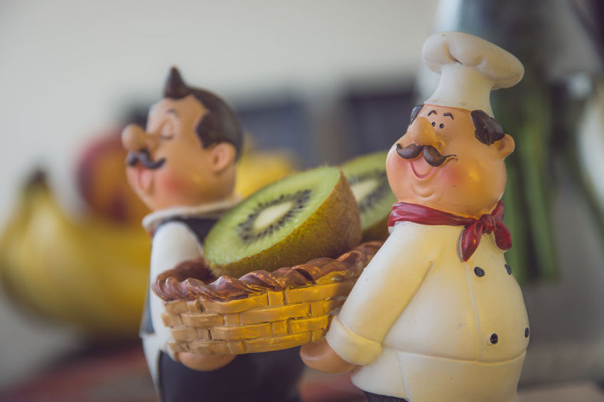 Figurines of chef and waiter holding a basket of kiwi fruit Art And Craft Chef Figurine  Focus On Foreground Food Fresh Fruit Fruit Basket Healthy Eating Kiwi - Fruit Male Likeness No People Palstic Sculpture Restaurant Waiter