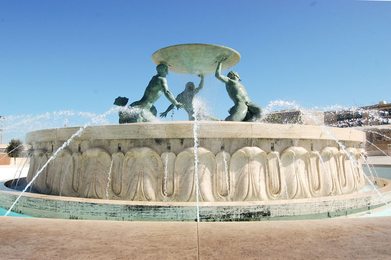 Statue of fountain against clear blue sky