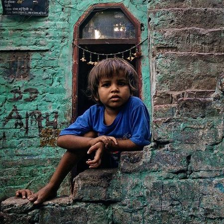 """An Indian boy poses for a photo at Katputli Nagar, New Delhi, India. (3/5) Many a times, I have been approached by kids urging me to take pictures of them. They shout, """"Ek photo! Ek photo!"""" (One photo, one photo). The glee on their faces at the prospect of getting photographed makes me more than happy to oblige. After photographing the children, I realised that their expressions and their poses make the pictures special to me. Everydayeverywhere Dailylife Photojournalism Journalism Indiaphotoproject Reportagespotlight _soi Dfordelhi Sodelhi DelhiGram Delhi Newdelhi ASIA India"""