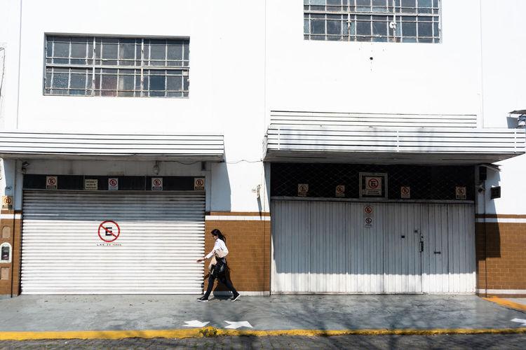 Full length of man walking on street against building
