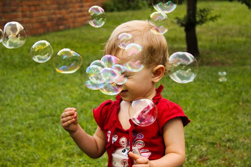 Baby girl playing with bubbles in lawn
