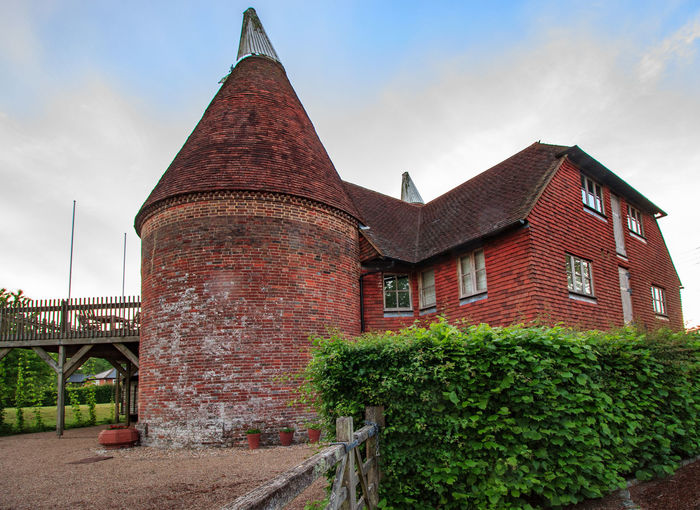 Oast house, Garden of England, Kent Architecture Built Structure Building Building Exterior Sky Cloud - Sky Nature No People Plant Tree Day Outdoors House Tower Connection Brick Old Window Roof Low Angle View Spire  Hedge Oast House Garden Of England Vivid International Rural Scene Village Farm Hops