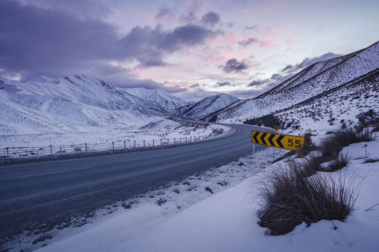Beauty In Nature Cloud - Sky Cold Temperature Communication Covering Mountain Nature No People Non-urban Scene Road Road Sign Scenics - Nature Sign Sky Snow Snowcapped Mountain Text Transportation Western Script Winter