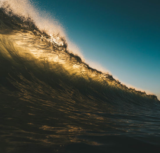 Waves Splashing In Sea Against Clear Sky During Sunset