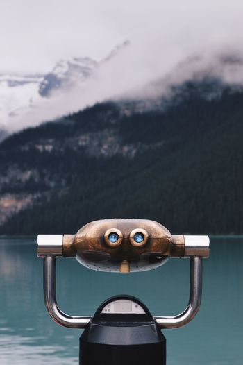 Coin-Operated Binoculars By Lake Against Mountain