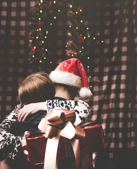 Girl hugging boyfriend holding a gift on Christmas eve Christmas Celebration Women Two People Holiday Lifestyles Females Decoration Rear View Love Family Positive Emotion Hug Christmas Lights Gift Happiness NewYear Mood Santa Santa Hat christmas tree #NotYourCliche Love Letter International Women's Day 2019