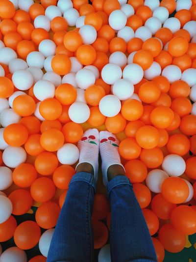 Low section of woman on orange and white balls