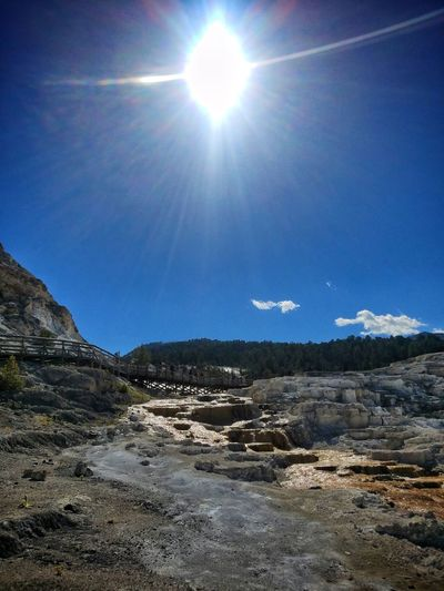 Mammoth Hot Springs is a chill place to be Mammothhotsprings Yellowstone National Park Whiterocks Freelance Hotspring Mountain Sun Sunlight Nature Beauty In Nature Outdoors Sky Landscape Tranquility Day No People Blue Scenics Mountain Range Clear Sky Rural Free Love Cool