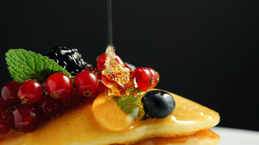 Stack of fresh fluffy pancakes decorated on top with forest berries and pouring honey syrup. Delicious, healthy american breakfast. Fresh bakery concept. Food Food And Drink Fruit Freshness Healthy Eating Berry Fruit Black Background Close-up Indoors  Still Life Studio Shot Wellbeing Indulgence Sweet Food No People Sweet Dessert Ready-to-eat Temptation Red Ripe Pancake Berries