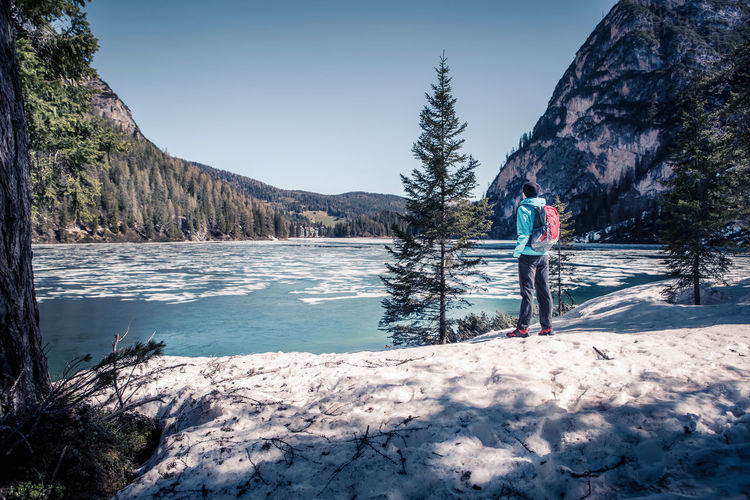 Rear View Full Length Of Man Standing By Lake During Winter