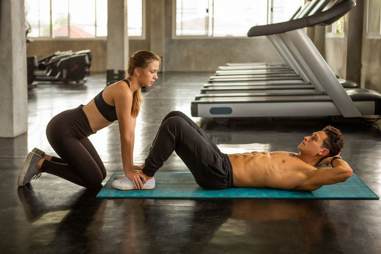 Side view of woman assisting man in exercising at gym